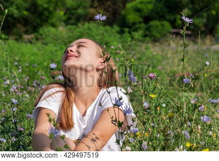 Young Happy Girl 16-17 Years Old, With Long Brown Hair, Laughing Happily In Nature Among The Wildflo