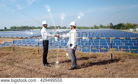 Asian Businessmen Standing Check Hand With The Solar Panel In The Background. The Idea Of Investors