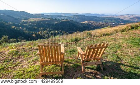 Two Wood Chairs Together Overlooking Scenic Mountains Valley With Forest Trees In Afternoon Blue Sky