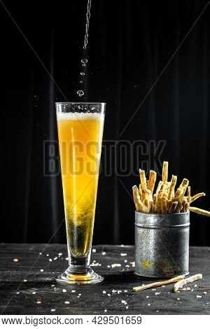 Pour Beer Into A Tall Glass With A Thick Foam, Dried Fish On Wooden Background. Beer Brewery Concept