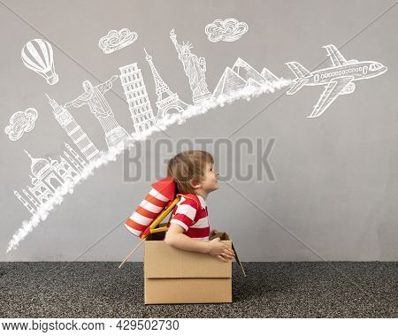 Child Playing At Home. Kid Sitting In Cardboard Box. Child Dreaming About Travel. Children Imaginati