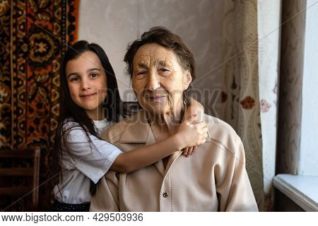 A Little Girl Is Laughing With Her Great-grandmother