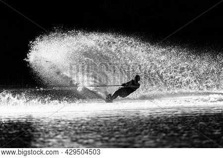 Waterski Young Man Unrecognizable Athlete Skiing Slalom Carves A Vertical Water Wake Spray  In Vinta