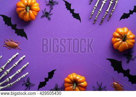 Halloween Decorations On Purple Background. Happy Halloween Concept. Flat Lay Pumpkins, Bony Hands,
