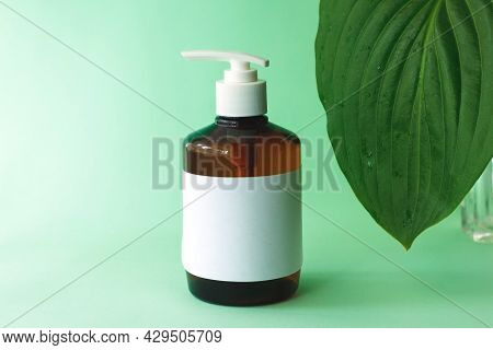 Brown Bottle Mockup For Bathing Products With Green Hosta Leave.