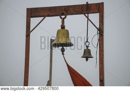 Stock Photo Of Two Ancient Copper Or Bronze Bell Hanging On A Orange Color Iron Frame At Hindu Templ