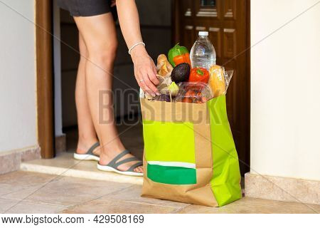 The Girl Ordered Groceries At Home. Delivery Of Groceries To The Hands Of The Girl Near The House. H