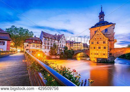 Bamberg, Bavaria. Old Town Hall, Obere Brucke And Regnitz River Dusk Illuminated. Germany City Break
