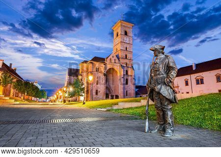 Alba Iulia, Romania. Night Scene With Walled Medieval City, Catholic Cathedral, Famous Travel Sight