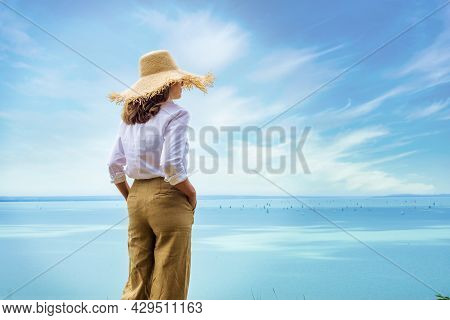 Shot Of Woman Wearing Straw Hat And White Shirt While Standing Outside And Looking At Sea View. Dayd