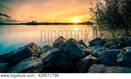 Sunset River Banks View Over The Water With Basalt Blocks And Reeds, Dutch Landscape Along The Ijsse