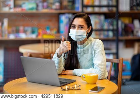 Everything Alright. Portrait Of Happy Woman With Surgical Medical Mask Working On Laptop In Cafe, Sh