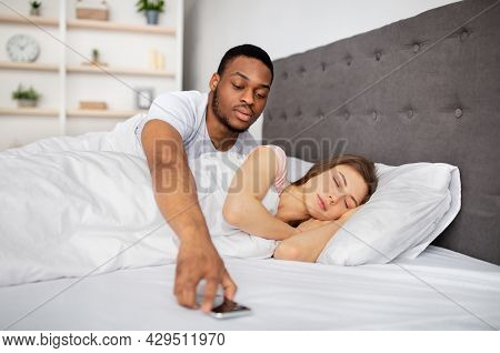Jealousy, Infidelity, Relationship Problems. Black Husband Checking Sleeping Wifes Mobile Phone In B