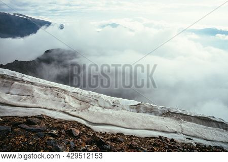 View From Precipice Edge With Snow Cornice Over Clouds To Mountain Vertex In Thick Clouds. Scenic La