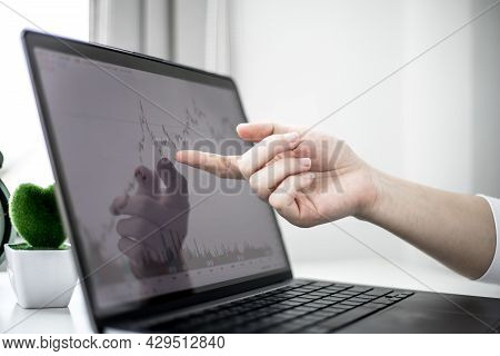 A Stock Investor Is Pointing To A Laptop Screen Running A Stock Chart Program To Read Stock Price Ch