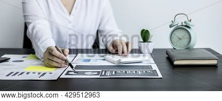 Close-up Of A Business Woman Holding A Pen And Pointing At A Financial Data Sheet And Pressing A Cal