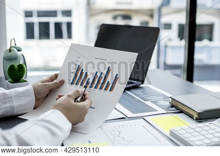 The Sales Manager Pointing At The Sales Document, She Is Reviewing The Monthly Sales Report Of The S