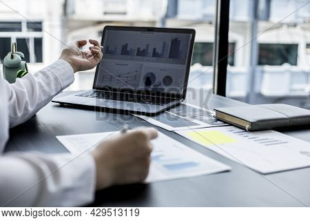 A Businesswoman Pointing At A Laptop Screen That Opens The Company's Annual Financial Summary Is Exa