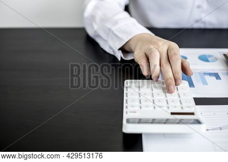 A Woman Pressing A White Calculator Is A Financial Expert Checking Company Financial Documents For T