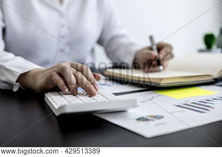 An Accounting Businesswoman Pressing The White Calculator And Taking Notes In Her Notebook, She Was