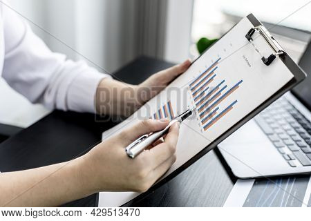 Woman Pointing To A Sales Data Sheet, A Sales Manager Is Looking At A Sales Summary Of Employees In