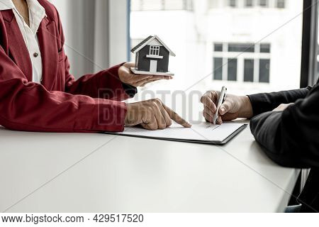 The Tenant Is Signing A Lease Agreement With The Landlord After Viewing The Home And Discussing The