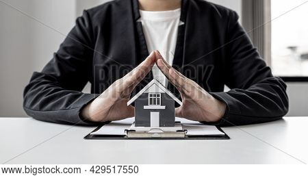 A Home Insurance Salesman Is Using His Hand To Make A Triangle Pose On The Small Gray Home Model As