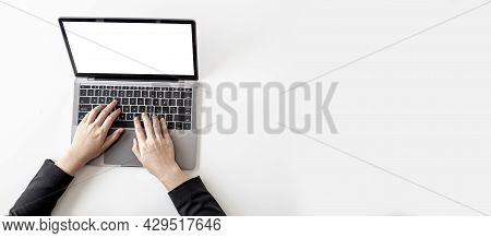 Top View A Businessman Is Typing On A Laptop Keyboard On His Desk. Panorama Banner Background With C