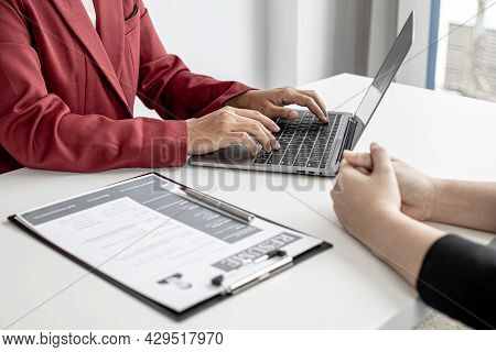 The Hr Department Is Typing A Laptop To Fill Out The Applicant's Information After Being Interviewed