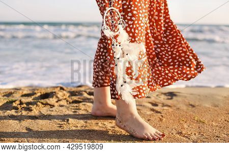 Cropped Photo Of Woman Walking Barefoot Along Seaside On Sand Beach With Dream Catcher Holding Down,