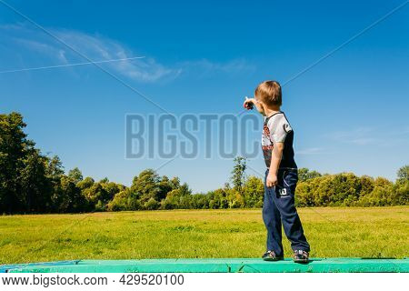 Little Boy Standing On Bench And Pointing At Flying Plane In Blue Summer Sky