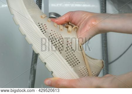 Woman Is Washing Sport Shoes In Bathroom By Hands, Closeup Hands. Laundry By Hands. She Is Cleaning