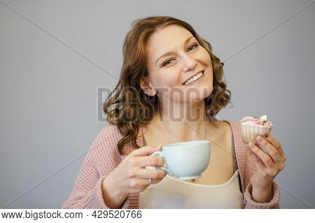 Happy Young Woman Eating Delicious Pink Cupcake With Toothy Smile And Closed Eyes After Taking Bite