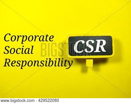 Business Concept.text Csr Writing On Colored Wooden Board On A Yellow Background.