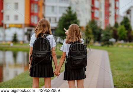 Two Pretty Teen Girls In Black And White School Uniform And Bags Going To School. View From The Back