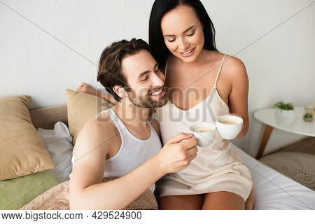 Happy Couple Clinking Cups Of Cappuccino In Bed.