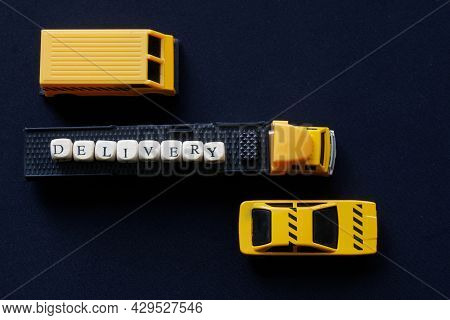Yellow Toy Truck With A Trailer And Delivery Among Other Vehicles. View From Above. The Concept Of T