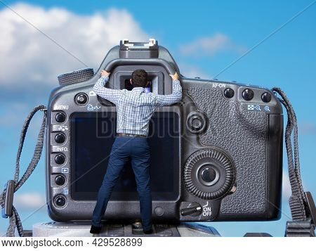 Giant Camera And Small Photographer. Surreal Concept