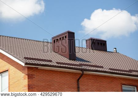 Red Metal Roof Tile And Smokestack. Modern Chimney On Brown Roof.