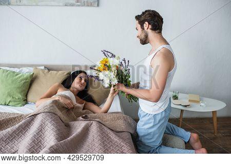 Man Holding Bouquet Of Flowers Near Happy Girlfriend In Bed.