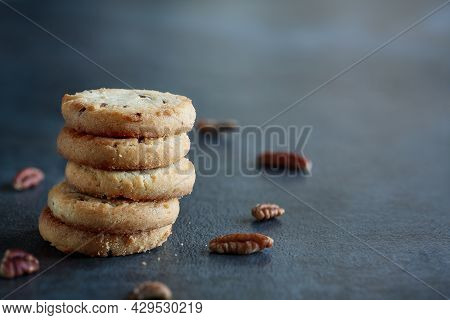 Stack Of Pecan Sandies Cookies Stacked On A Dark Table. Selective Focus With Blurred Foreground And
