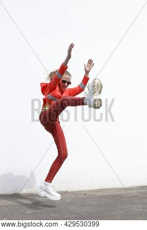 A Girl Jumps Against The Background Of A Wall In The City.