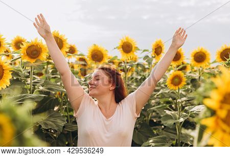 Happy Free Woman Opened Arms Walking In Blooming Sunflower Field. The Concept Of Freedom. Young Woma