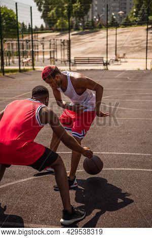 Young African American Sportsmen Playing Basketball On Court At Daytime.