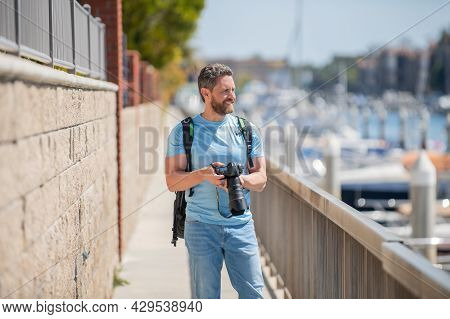 Man Hold Camera Standing On Promenade. Vacation Photography. Travel Photography