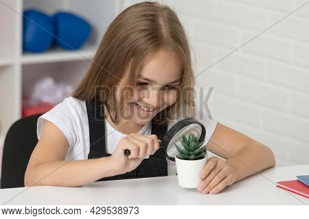 Teen Girl Looking At Plant Through Magnifier. Back To School. Study Biology. Research Education