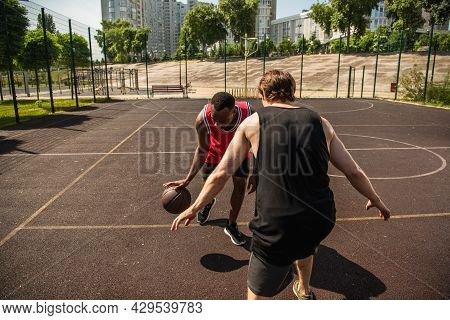Multiethnic Men Playing Basketball On Outdoor Playground At Daytime.