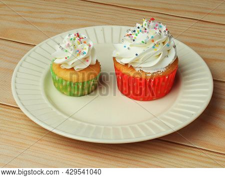 Different Types Of Vanilla Cupcakes With White Butter Cream Frosting And Sprinkles On White Plate Fo