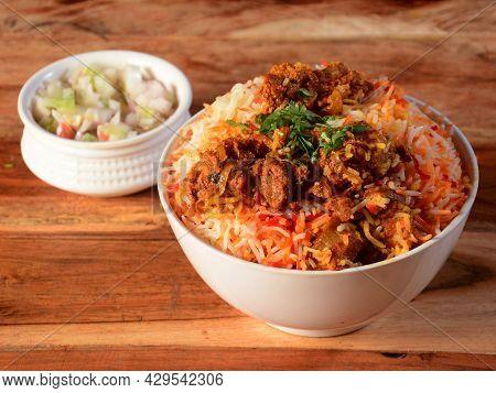 Kashmiri Mutton Gosht Or Lamb Biryani Prepared In Basmati Rice Served With Onion Over Rustic Wooden