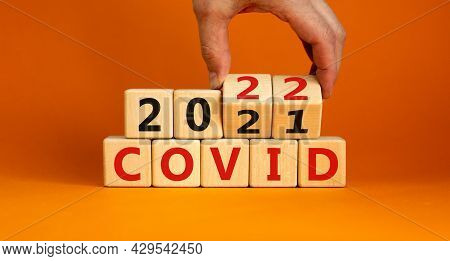 Symbol Of Covid-19 Pandemic In 2022. Doctor Turns Wooden Cubes And Changes Words 'covid 2021' To 'co